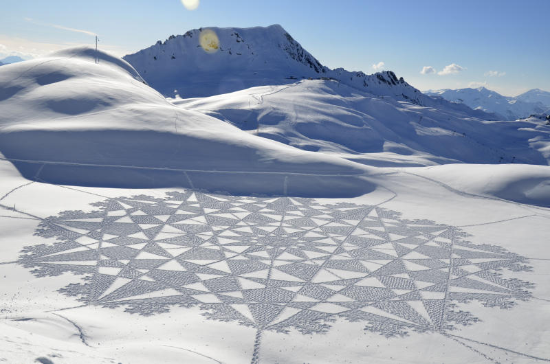 In this 2014 photo, provided by Simon Beck Snow Art, is one of Beck's pieces in the snow at the Les Arcs ski resort in southeastern France. Using a compass, snowshoes and his background as a cartographer and competitive orienteer, the 61-year-old British artist and a handful of volunteers recently tromped across the frozen reservoir near Silverthorne, Colo., a resort town west of Denver, to create a massive, geometrical design on a fresh canvas of snow. (Simon Beck Snow Art via AP)