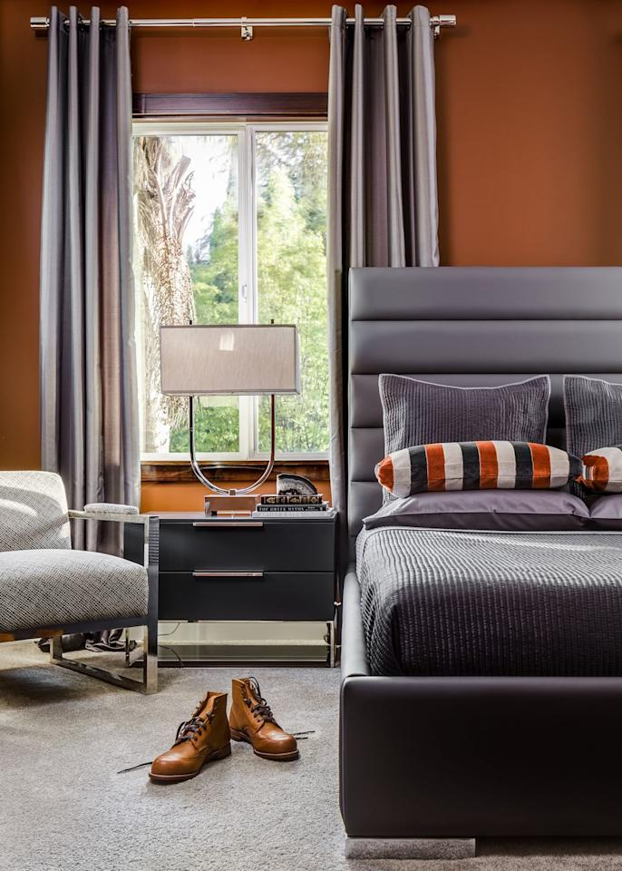 "<p>Invigorating burnt sienna walls warm up this masculine bedroom by Kesha Franklin of <a href=""https://haldeninteriors.com/"" target=""_blank"">Halden Interiors</a>. The earthy orange tone complements the moody cool grays of the upholstery and asserts a cozy vibe.  </p>"