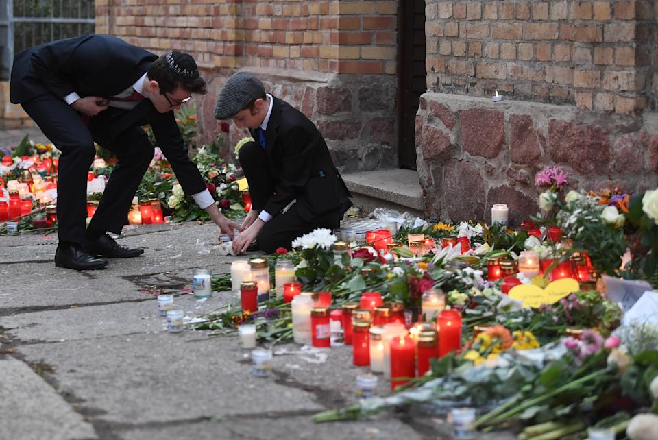 11 October 2019, Saxony-Anhalt, Halle/Saale: Two men lay flowers and candles on the wall of the synagogue. On 09.10.2019, two people were shot dead during an attack by an extreme right-wing perpetrator in front of a synagogue in Halle. Photo: Hendrik Schmidt/dpa (Photo by Hendrik Schmidt/picture alliance via Getty Images)