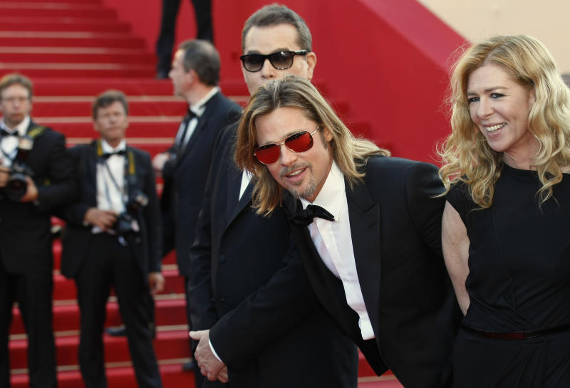 Actor Brad Pitt, center, actress Dede Gardner, right and actor Ray Liotta, partially seen arrive for the screening of Killing Them Softly at the 65th international film festival, in Cannes, southern France, Tuesday, May 22, 2012. (AP Photo/Lionel Cironneau)