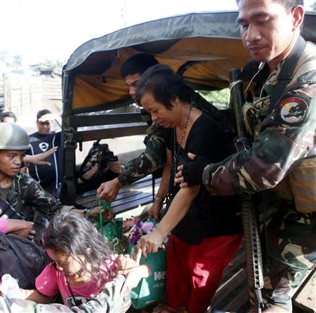 Government soldiers help former hostages of the Muslim rebels of Moro National Liberation Front (MNLF) after they were released from their one-week captivity in Zamboanga city, in southern Philippines September 17, 2013. REUTERS/Erik De Castro