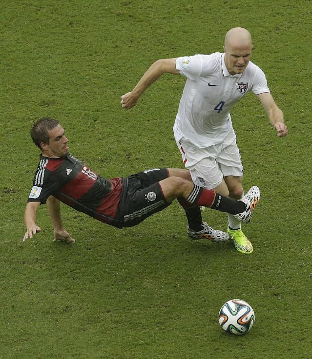 Germany's Philipp Lahm challenges United States' Michael Bradley (4) for the ball during the group G World Cup soccer match between the USA and Germany at the Arena Pernambuco in Recife, Brazil, Thursday, June 26, 2014. (AP Photo/Hassan Ammar)