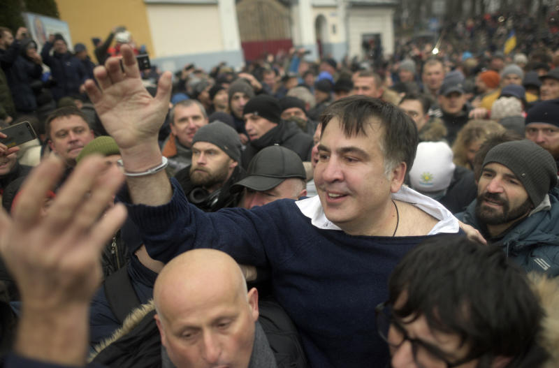"""Former Georgian president Mikheil Saakashvili, center, greets protesters after he escaped with help from supporters and led them on a march toward parliament, where they planned to call for President Petro Poroshenko to resign in Kiev, Ukraine, Tuesday, Dec. 5, 2017. Hundreds of protesters chanting """"Kiev, rise up!"""" blocked Ukrainian police as they tried to arrest former Georgian president Mikheil Saakashvili on Tuesday. (AP Photo/Evgeniy Maloletka)"""