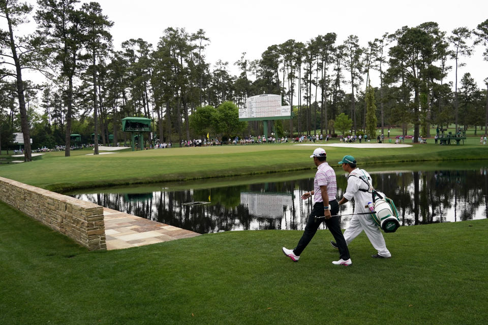 Hideki Matsuyama, of Japan, walks with his caddie Shota Hayafuji to the 15th green during the second round of the Masters golf tournament on Friday, April 9, 2021, in Augusta, Ga. (AP Photo/David J. Phillip)