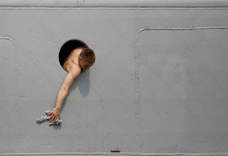 A Russian sailor cleans the navy ship Admiral Vinogradov from a porthole of the vessel during a port visit in Manila, Philippines October 20, 2017. REUTERS/Dondi Tawatao