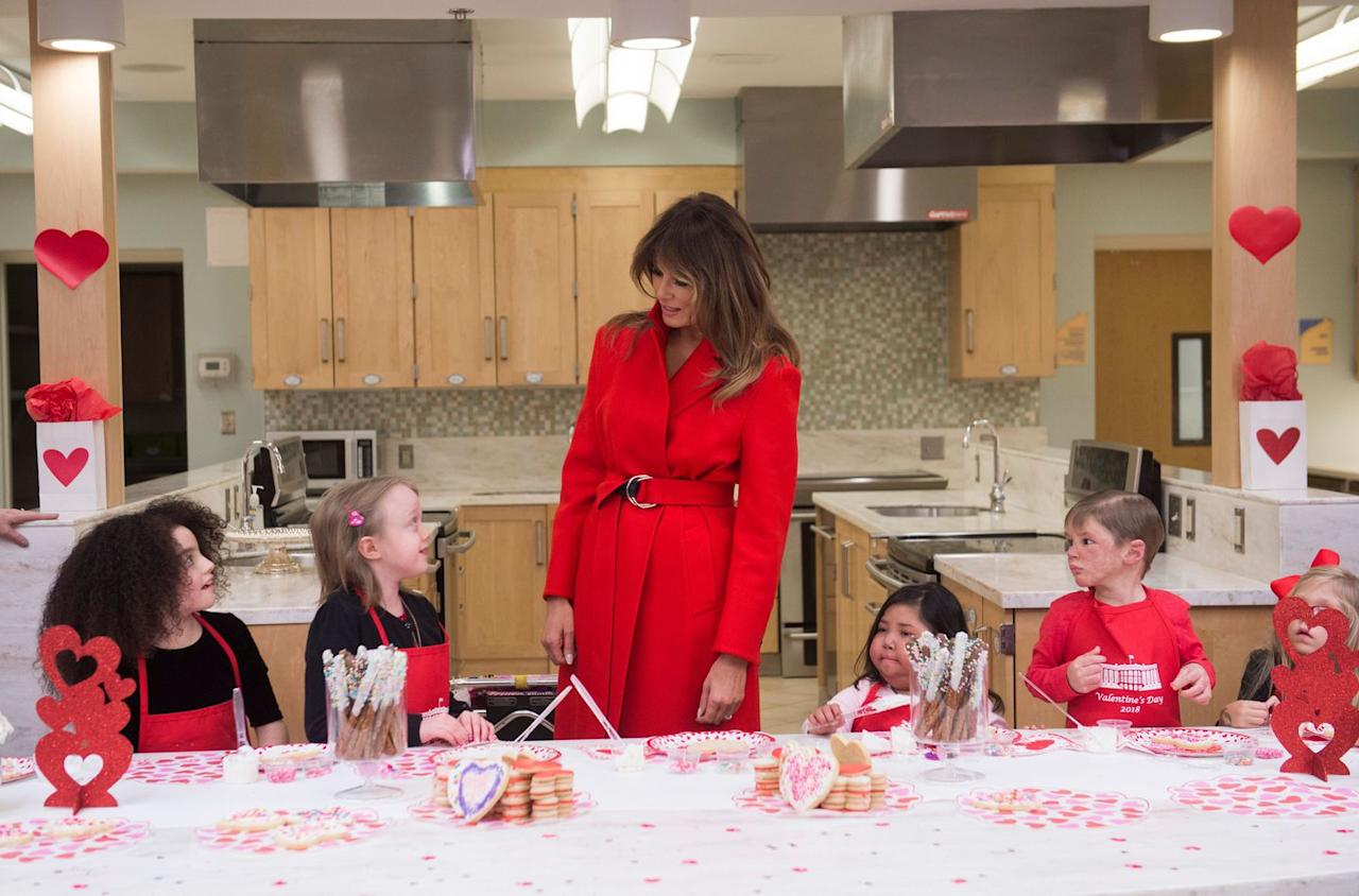 The First Lady spent Valentine's Day visiting young patients at the National Institutes of Health's Children's Inn. She wore a bright red coat for the occasion.