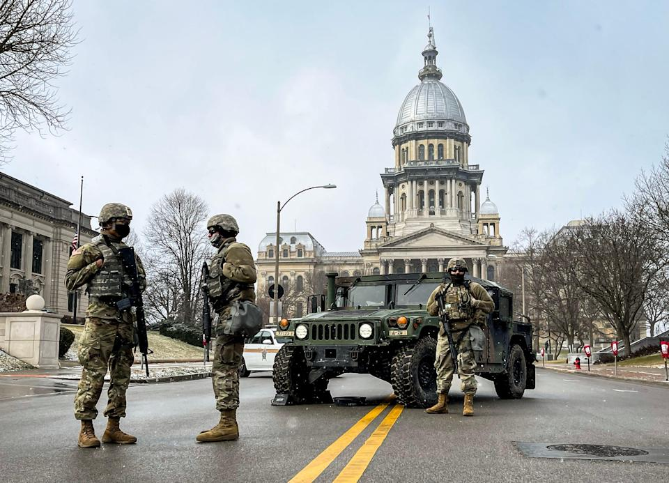 Members of the Illinois National Guard stand posted at a road closure along East Capitol Avenue in front of the Illinois State Capitol on Jan. 17, 2021, in Springfield, Ill.