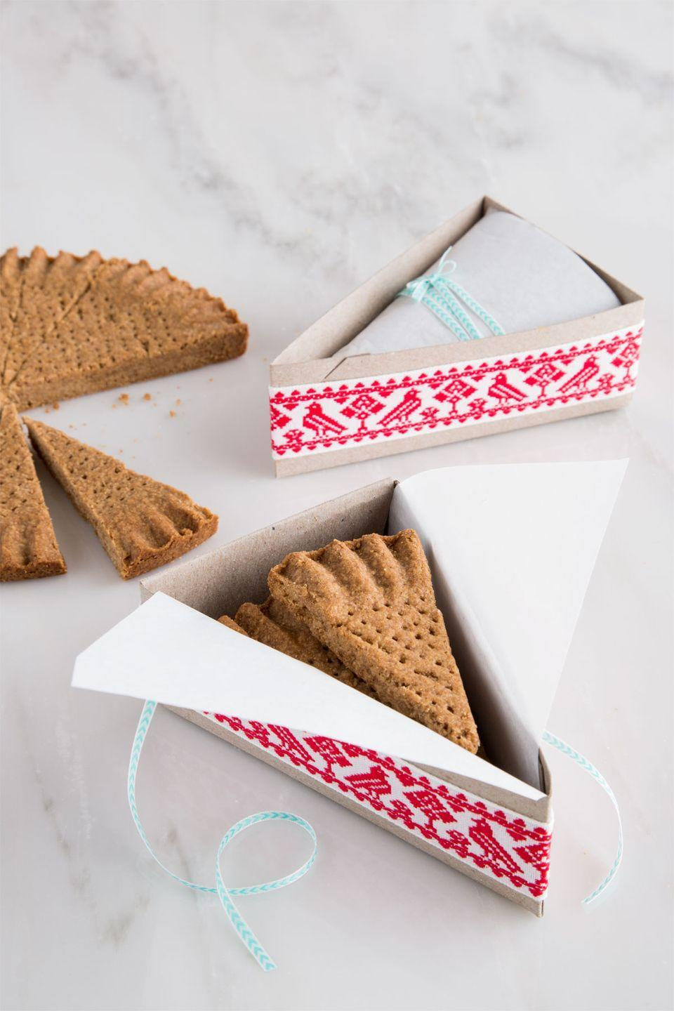 "<p>Wrap the edges of a cardboard pie slice box with decorative ribbon. Wrap cookies in parchment, then secure with ribbon and tuck inside box.</p><p><a href=""https://www.countryliving.com/food-drinks/recipes/a36900/spiced-shortbread/"" rel=""nofollow noopener"" target=""_blank"" data-ylk=""slk:Get the recipe."" class=""link rapid-noclick-resp""><strong>Get the recipe.</strong></a></p><p><a class=""link rapid-noclick-resp"" href=""https://go.redirectingat.com?id=74968X1596630&url=https%3A%2F%2Fwww.etsy.com%2Flisting%2F223519166%2Fpie-slice-box-for-weddings-picnics&sref=http%3A%2F%2Fwww.countryliving.com%2Ffood-drinks%2Fg647%2Fholiday-cookies-1208%2F"" rel=""nofollow noopener"" target=""_blank"" data-ylk=""slk:SHOP PIE SLICE BOXES"">SHOP PIE SLICE BOXES</a></p>"
