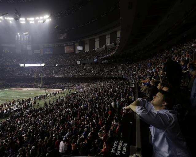 A fan looks around the Superdome after half the lights went out during a power outage in the second half of the NFL Super Bowl XLVII football game between the San Francisco 49ers and Baltimore Ravens on Sunday, Feb. 3, 2013, in New Orleans. (AP Photo/Gerald Herbert)