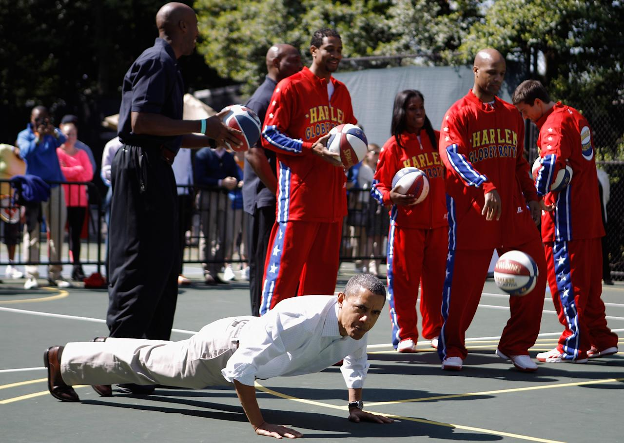 U.S. President Barack Obama does pushups as the Harlem Globe Trotters watch during the White House Easter Egg Roll on the South Lawn of the White House on April 9, 2012 in Washington, DC. Thousands of people people are expected to attend the 134-year-old tradition of rolling colored eggs down the White House lawn that was started by President Rutherford B. Hayes in 1878.  (Photo by Chip Somodevilla/Getty Images)