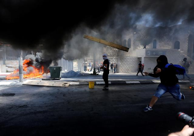 <p>Palestinian protestors burn tyres and throw rocks with slingshots in response to Israeli forces' intervention during a protest, organized to mark 70th anniversary of Nakba, also known as Day of the Catastrophe in 1948, and against United States' plans to relocate the U.S. Embassy from Tel Aviv to Jerusalem in Bethlehem, West Bank on May 15, 2018. (Photo: Wisam Hashlamoun/Anadolu Agency/Getty Images) </p>