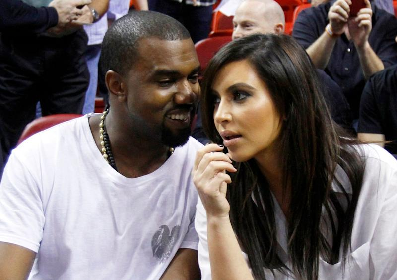 FILE - This Dec. 6, 2012 file photo shows singer Kanye West, left, talks to his girlfriend Kim Kardashian before an NBA basketball game between the Miami Heat and the New York Knicks in Miami. As the tabloids speculated over whether or not Jessica Simpson was expecting her second baby and the media zeroed in on Kate Middleton's pregnancy, Kardashian admits it was nice to be away from the glare of the spotlight as she was in the early stages of her own pregnancy. Now that the word is out, 32-year-old Kardashian says her motherly instincts have made her pull back from being so open about her personal life. (AP Photo/Alan Diaz, file)