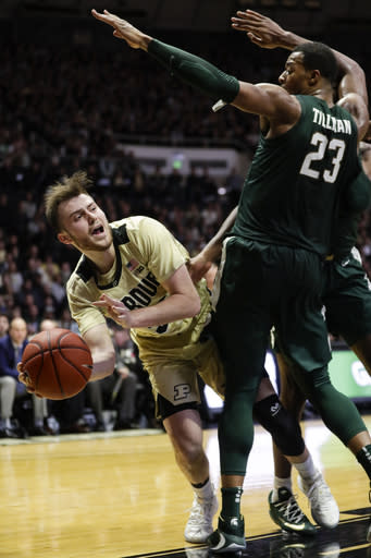 Purdue guard Sasha Stefanovic, left, passes around Michigan State forward Xavier Tillman (23) during the second half of an NCAA college basketball game in West Lafayette, Ind., Sunday, Jan. 12, 2020. (AP Photo/Michael Conroy)