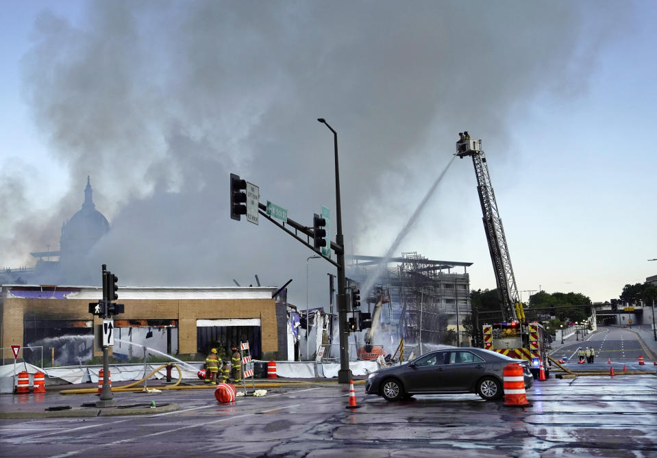 Firefighters battle a fire in downtown St. Paul, Minn., that has engulfed a building that was under construction on Tuesday, Aug. 4, 2020. There were no reports of injuries and there was no immediate word about the possible cause of the fire. (David Joles /Star Tribune via AP)