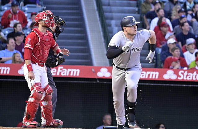 New York Yankees' Luke Voit, right, runs to first as he hits a solo home run while Los Angeles Angels catcher Jonathan Lucroy looks on during the first inning of a baseball game Monday, April 22, 2019, in Anaheim, Calif. (AP Photo/Mark J. Terrill)