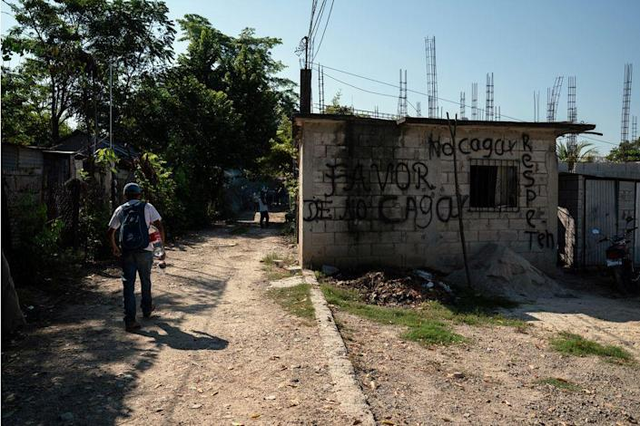"Migrants walk towards the train station near Palenque, Chiapas, on Oct. 26. The graffiti reads, ""Please do not sh-t here. Be respectful."""