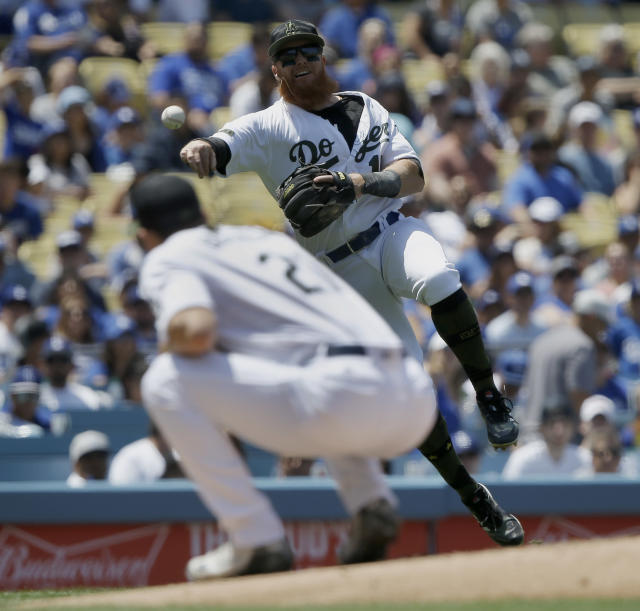 Los Angeles Dodgers third baseman Justin Turner, right, throws over starting pitcher Walker Buehler but not in time to get out San Diego Padres' Jose Pirela on an infield single during the fourth inning of a baseball game in Los Angeles, Sunday, May 27, 2018. (AP Photo/Alex Gallardo)