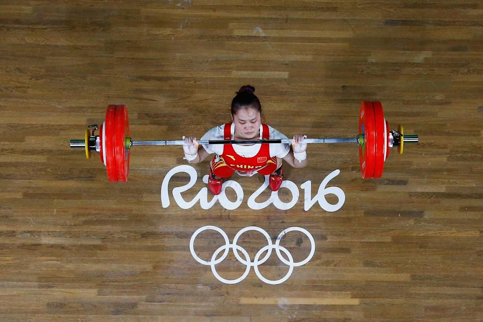 <p>Wei Deng of China lifts to secure winning the gold medal during the Women's 63kg Group A Weightlifting contest on Day 4 of the Rio 2016 Olympic Games at the Riocentro – Pavilion 2 on August 9, 2016 in Rio de Janeiro, Brazil. (Photo by Pool/Getty Images) </p>