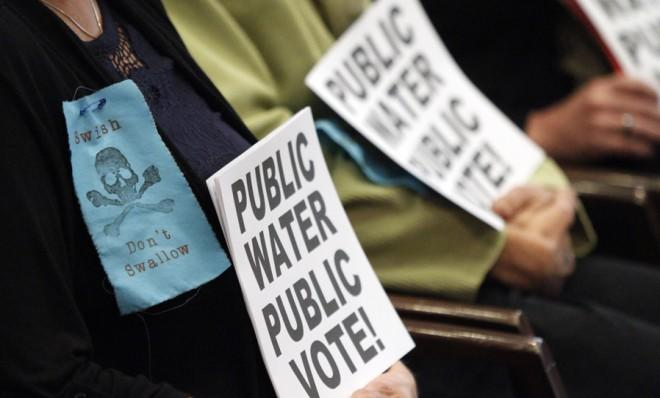Protestors hold signs in Portland's City Hall during a 2012 vote to add fluoride to the city water.