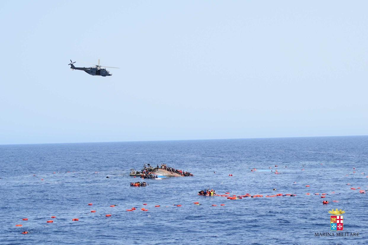 SICILIAN STRAIT, MEDITERRANEAN SEA - MAY 25: A helicopter approaches to the capsized boat as Italian marines rescue migrants from an overcrowded boat at Sicilian Strait, between Libya and Italy, in Mediterranean sea on May 25, 2016. The Italian Navy saved around 500 migrants as they found dead bodies of seven migrants in the sea during the operations. (Photo by Italian Navy / Marina Militare/Anadolu Agency/Getty Images)
