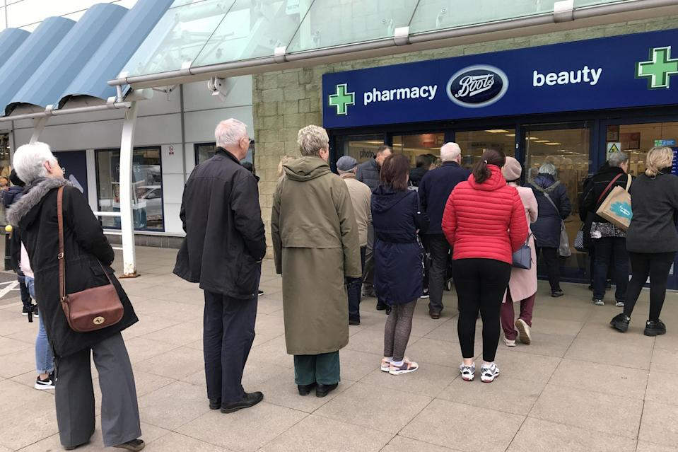 People queue outside a Boots pharmacy store in west London where stocks of hand sanitiser are limited to two per person (PA)