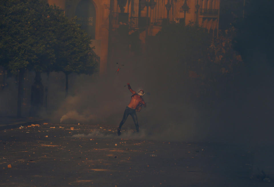 An anti-government protester throws a stone amid tear gas fired by riot police during a protest marking the first anniversary of the massive blast at Beirut's port, near Parliament Square, In Beirut, Lebanon, Wednesday, Aug. 4, 2021. United in grief and anger, families of the victims and other Lebanese came out into the streets of Beirut on Wednesday to demand accountability as banks, businesses and government offices shuttered to mark one year since the horrific explosion. (AP Photo/Bilal Hussein)