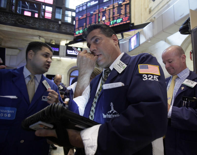 Trader William McInerney, center, works on the floor of the New York Stock Exchange Tuesday, July 31, 2012.  U.S. stocks are opening mostly lower ahead of a two-day policy meeting at the Federal Reserve. (AP Photo/Richard Drew)