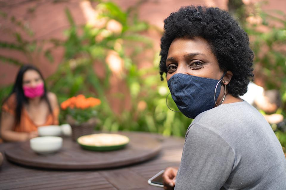 Portrait of woman using protective mask in the backyard