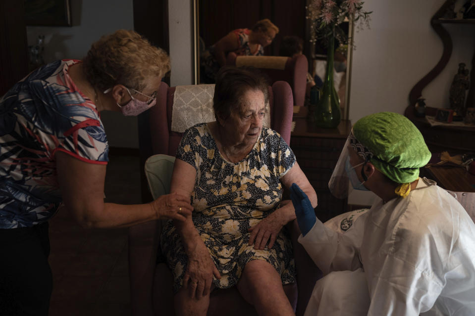 In this Friday, July 31, 2020 file photo, Dr. Marta Ruberte, right, talks to 94-year-old Maria Lluisa Olivella during a home visit in Sant Sadurní d'Anoia, Catalonia region, Spain. Olivella was feeling tired but according to the Doctor is not suspected of having coronavirus. In contrast to the darkest weeks of March and April, when the virus ripped through Spain's elderly in nursing homes and pushed the country's hospitals to the breaking point, the pressure is now on Spain's neighborhood health clinics. (AP Photo/Felipe Dana)