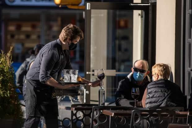 A waiter serves diners at an outside patio during a moment of sun in Vancouver in January 2021.  (Ben Nelms/CBC - image credit)