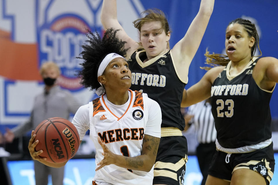 Mercer guard Amoria Neal-Tysor (1) drives the ball to the basket past Wofford guard Annabelle Schultz (1) and Wofford forward Lawren Cook (23) in the first half of an NCAA women's college basketball championship game for the Southern Conference tournament, Sunday, March 7, 2021, in Asheville, N.C. (AP Photo/Kathy Kmonicek)
