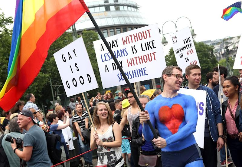 US embassy employee Tim Standaert waves a rainbow US flag as he attends the Gay Pride parade in Berlin on June 27, 2015 (AFP Photo/Adam Berry)