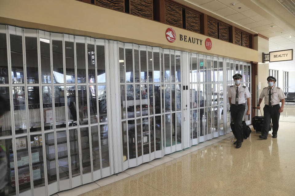 Flight crew walk past a closed duty-free shop inside the Daniel K. Inouye International Airport Thursday, Oct. 15, 2020, in Honolulu. The COVID-19 pandemic has caused a devastating downturn on Hawaii's tourism-based economy. Many stores and restaurants inside the airport remain close due the the economic crisis. (AP Photo/Marco Garcia)