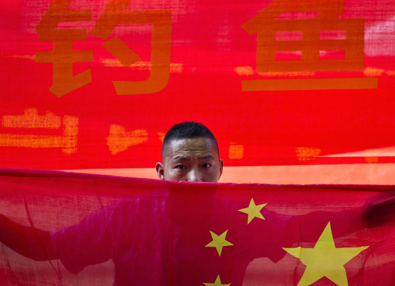 A Chinese man holds a national flag during a protest outside the Japanese Embassy in Beijing Wednesday, Aug. 15, 2012. Chinese hold a protest against Japan plans to nationalize disputed islands, which also claimed by Taiwan and China. The islands called Senkaku in Japanese and Diaoyu in Chinese have long been a source of tension in the region. (AP Photo/Andy Wong)