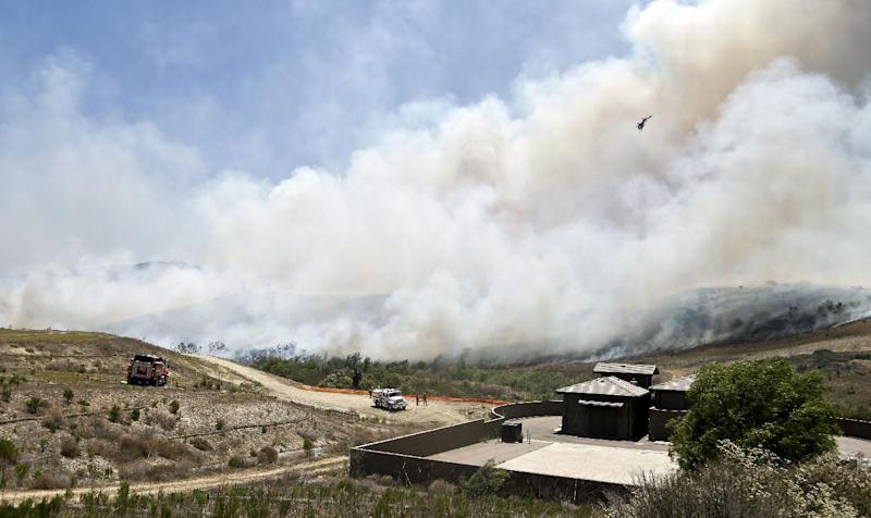 Smoke rises from a canyon where a wild fire is burning Tuesday, May 13, 2014, in San Diego. Wildfires destroyed a home and forced the evacuation of several others Tuesday in California as a high-pressure system brought unseasonable heat and gusty winds to a parched state that should be in the middle of its rainy season. (AP Photo)