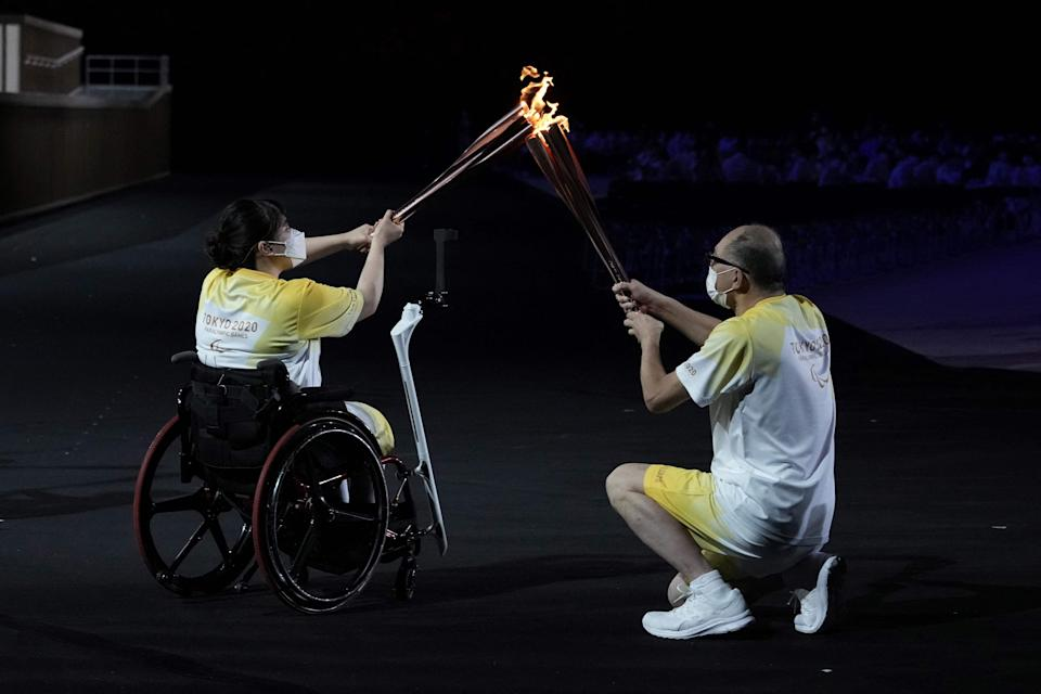 The Paralympic flame is passed between torchbearers during the opening ceremony for the Tokyo Paralympic Games at the Olympic Stadium on Aug. 24.