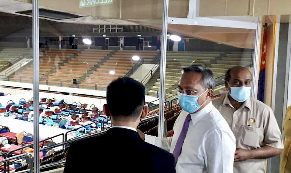 Johor Mentri Besar Datuk Hasni Mohammad (centre) and Johor Health and Environment Committee chairman R. Vidyananthan (right) are briefed by Zaki on the operations of the Covid-19 Quarantine and Treatment Centre at the Pasir Gudang City Council Indoor Stadium in Pasir Gudang today. — Picture by Ben Tan