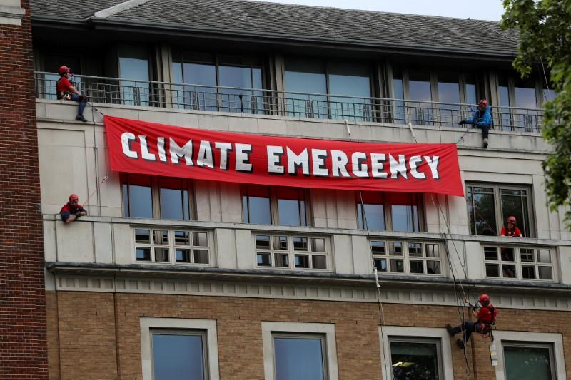 FILE PHOTO: Greenpeace activists hang from ropes as they unfurl a banner on the BP headquarters in London