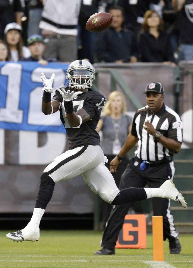 Oakland Raiders wide receiver Denarius Moore (17) catches a 36-yard touchdown pass from quarterback Derek Carr during the first quarter of an NFL preseason football game against the Seattle Seahawks in Oakland, Calif., Thursday, Aug. 28, 2014. (AP Photo/Ben Margot)