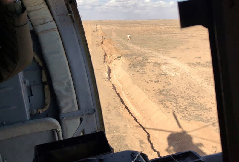 Iraqi vehicles dig a new trench along the border with eastern Syria