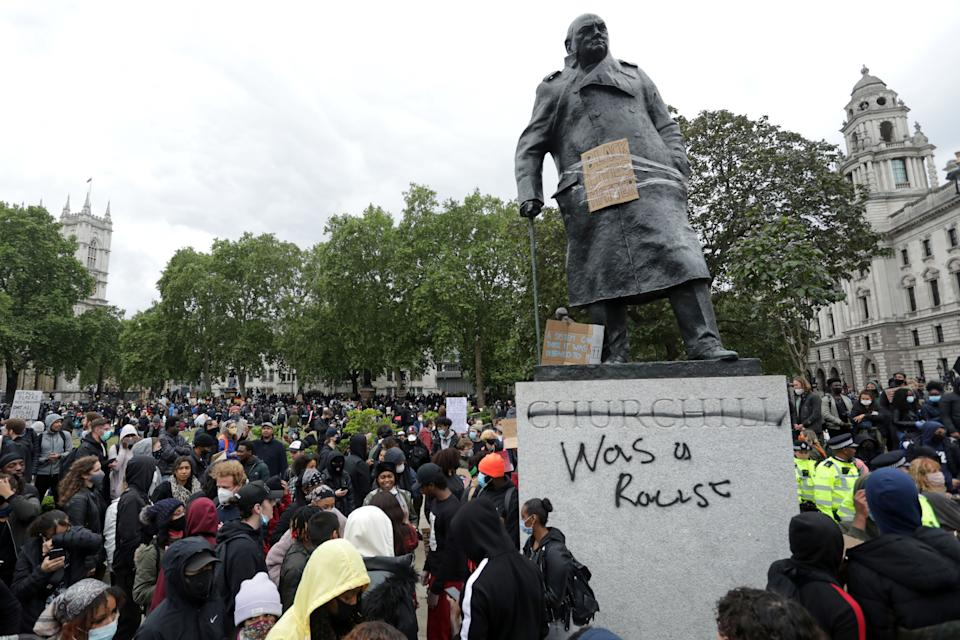 """TOPSHOT - The statue of former British prime minister Winston Churchill is seen defaced, with the words (Churchill) """"was a racist"""" written on it's base in Parliament Square, central London after a demonstration outside the US Embassy, on June 7, 2020, organised to show solidarity with the Black Lives Matter movement in the wake of the killing of George Floyd, an unarmed black man who died after a police officer knelt on his neck in Minneapolis. - Taking a knee, banging drums and ignoring social distancing measures, outraged protesters from Sydney to London on Saturday kicked off a weekend of global rallies against racism and police brutality. (Photo by ISABEL INFANTES / AFP) (Photo by ISABEL INFANTES/AFP via Getty Images)"""