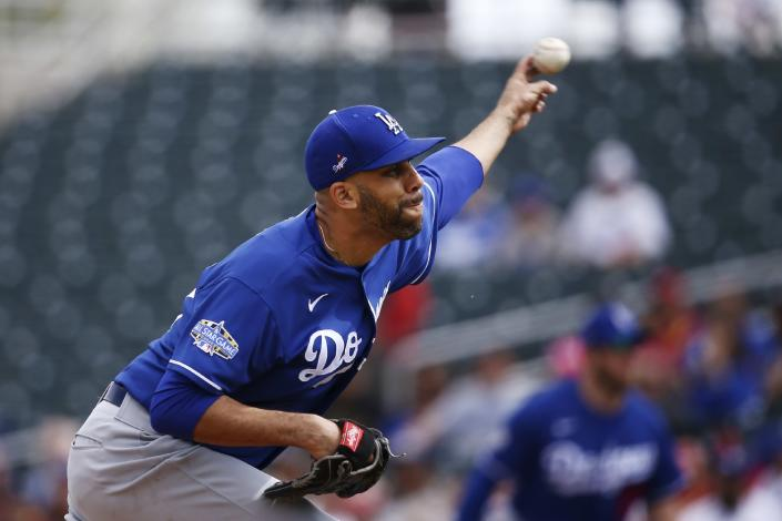 FILE - In this March 2, 2020, file photo, Los Angeles Dodgers starting pitcher David Price throws against the Cincinnati Reds during the first inning of a spring training baseball game in Goodyear, Ariz. Price, Buster Posey, Marcus Stroman and more than a dozen other players who opted out of the pandemic-shortened 2020 season get back to work this week. They not only will have to deal with rust but the demands of MLB's coronavirus safety protocols. (AP Photo/Ross D. Franklin, File)