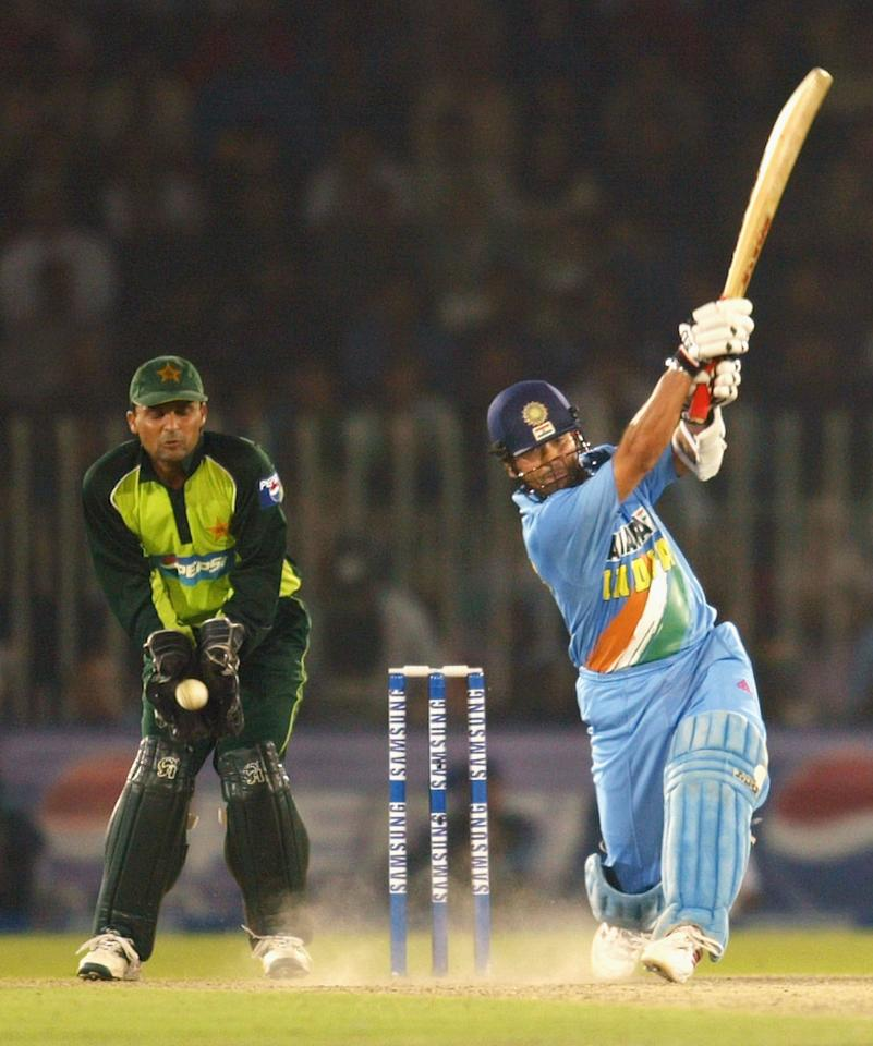 RAWALPINDI, PAKISTAN - MARCH 16:  Sachin Tendulkar (R) of India hits out during his innings of 141 as wicketkeeper Moin Khan of Pakistan watches during the second ODI between Pakistan and India, played at Pindi Cricket Stadium March 16, 2004, in Rawalpindi, Pakistan. It is the Indian team's first full tour of Pakistan in almost 15 years, comprising five one-day internationals followed by three Tests. The tour is seen as evidence that the two nuclear-armed rivals are getting closer after almost going to war over the Himalayan region of Kashmir less than two years ago. (Photo by Scott Barbour/Getty Images)
