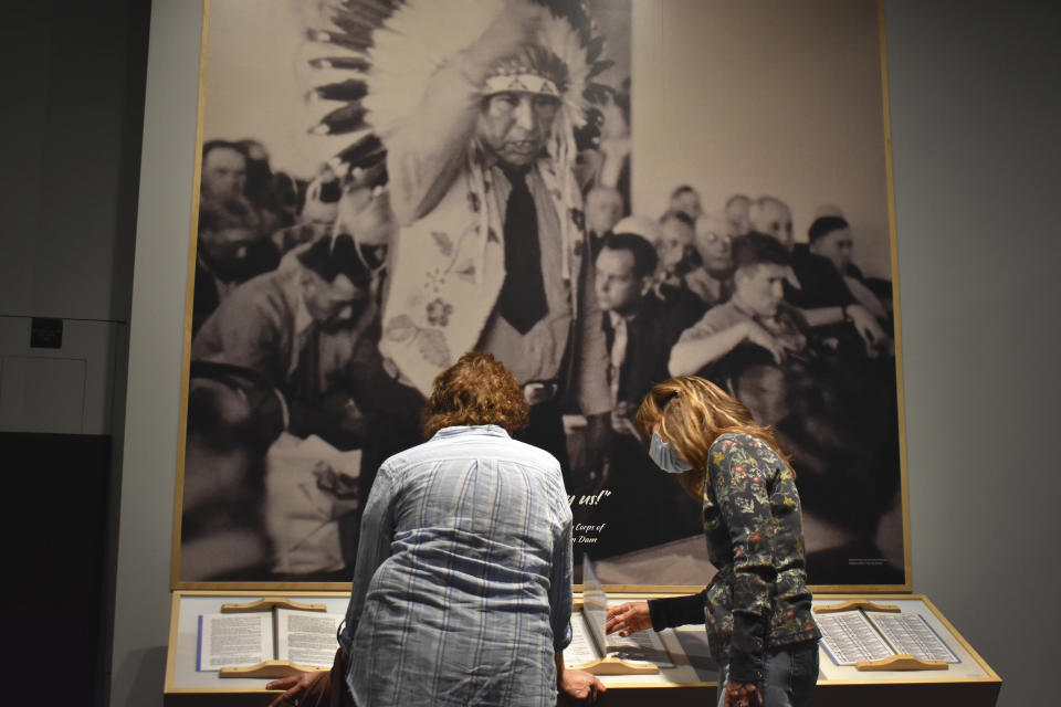 In this Wednesday, May 19, 2021, photo, people tour an exhibit showing a photo of late Chief Thomas Spotted Wolf at a hearing objecting to the construction of Garrison Dam, at the MHA Nation Interpretive Center on the Fort Berthold Indian Reservation in New Town, North Dakota. The $30 million cultural center in New Town pieces together the tribes' fractured past through displays and artifacts. A sound studio captures stories from elders who lived through dam construction and flooding of 135,000 acres (55,000 hectares) along the Missouri. (AP Photo/Matthew Brown)