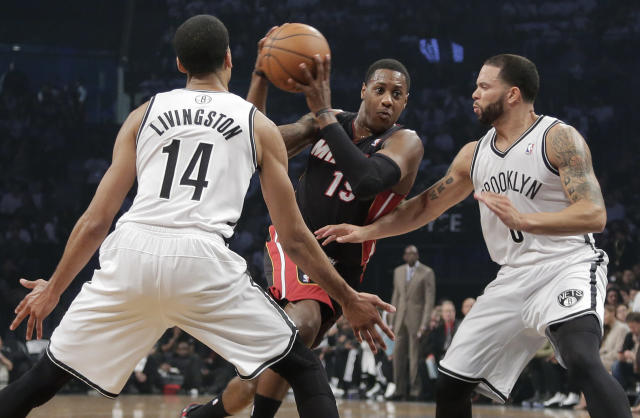 Miami Heat guard Mario Chalmers (15) drives against Brooklyn Nets guards Shaun Livingston (14) and Deron Williams (8) in the second period during Game 3 of an Eastern Conference semifinal NBA playoff basketball game on Saturday, May 10, 2014, in New York. (AP Photo/Julie Jacobson)