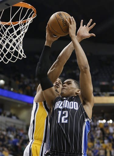 Orlando Magic's Tobias Harris (12) is fouled by Indiana Pacers' Gerald Green as he goes up for a dunk during the first half of an NBA basketball game Tuesday, March 19, 2013, in Indianapolis. (AP Photo/Darron Cummings)