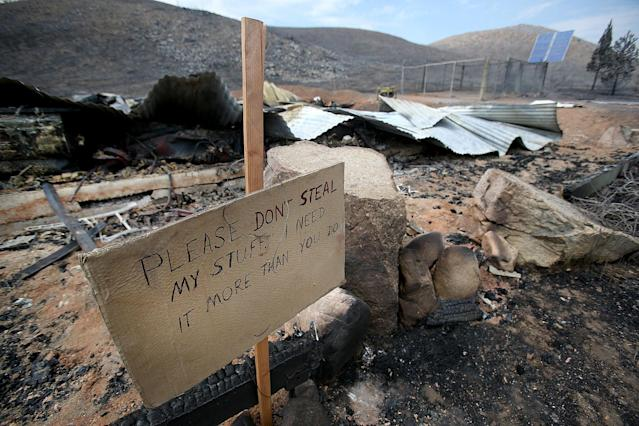 A sign is posted Tuesday, Aug. 13, 2013 by the remains of Bill Corlett's home that burned during a wildfire on Aug. 8, 2013 northwest of Fairfield, Idaho. More than 50 structures have burned in the past week in Idaho wildfires. (AP Photo/The Times-News, Ashley Smith) MANDATORY CREDIT