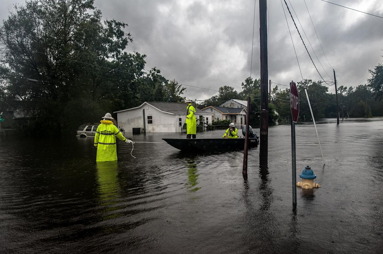 Workers with Duke Energy move through Lumberton by boat in an effort to restore power to customers on Sunday after intense flooding in the town.