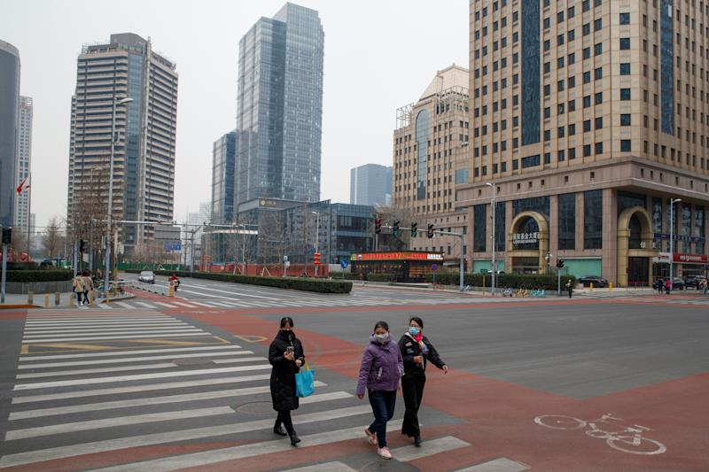 People cross an empty street in the Central Business District in Beijing as the country is hit by an outbreak of the novel coronavirus. Source: Reuters/Thomas Peter