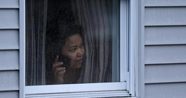 A woman looks out a window at her home as police start to search an apartment building while looking for a suspect in the Boston Marathon bombings in Watertown, Mass., Friday, April 19, 2013. Two suspects in the Boston Marathon bombing killed an MIT police officer, injured a transit officer in a firefight and threw explosive devices at police during their getaway attempt in a long night of violence that left one of them dead and another still at large Friday, authorities said as the manhunt intensified for a young man described as a dangerous terrorist. (AP Photo/Charles Krupa)